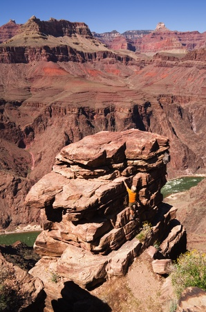 plateau point: a man climbing a rock pinnacle at Plateau Point in the Grand Canyon Stock Photo