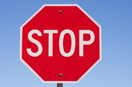 stop sign on metal post with blue sky background Stock Photo - 16566692