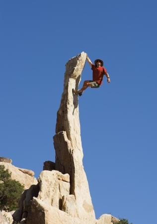 rockclimber: a man climbing up a steep narrow rock spire