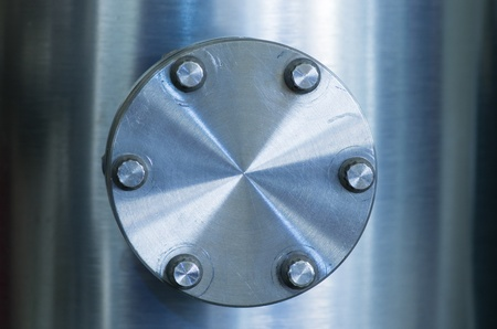 tight focus: bolted on flange cover on an industrial brushed metal vacuum pipe Stock Photo