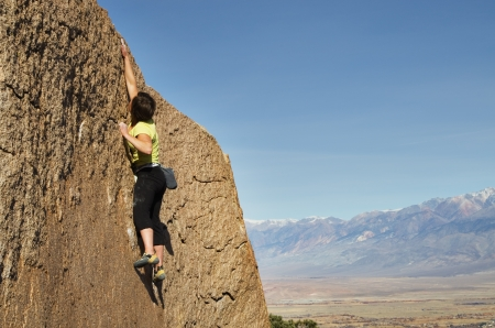 a woman rock climber makes a big reach for the top Stock Photo - 19457219