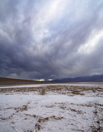 badwater in Death Valley salt pan with dramatic gray clouds photo