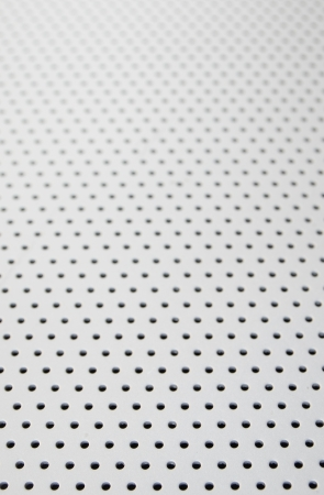 background texture with holes in metal with selective focus in the foreground Stock Photo - 19586515