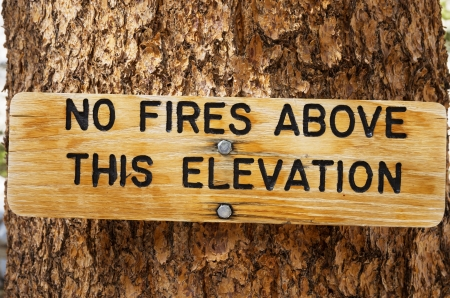 no fires: no fires above this elevation wood sign on a tree trunk