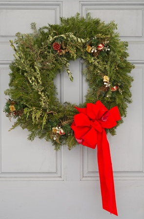 Christmas wreath with red ribbon on a gray door Stock Photo - 20436457
