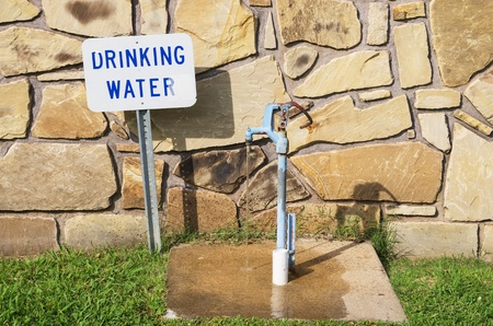 drinking water tap with sign and running water behind a stone wall Stock Photo - 21651950