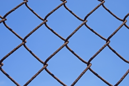 detail of a rusty chain link fence with blue sky background Stock Photo - 21652008