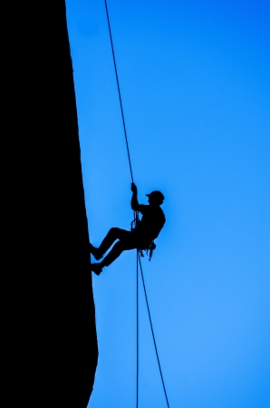 silhouette of man rappelling down an overhanging cliff with blue sky background