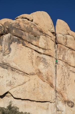 double cross: a rock climbing man leading Double Cross rock climb in Joshua Tree National Park