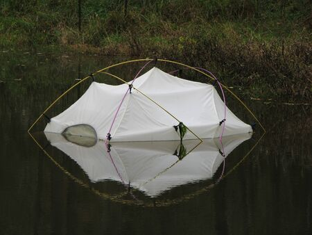 a tent partially submerged in a pond with reflection