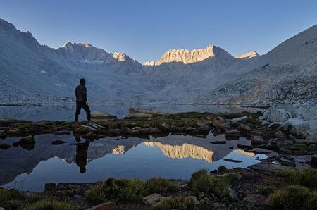 john muir wilderness: un hombre mirando a la ma�ana la vista sobre el lago de monta�a de nieve a Mount Mills en la Sierra Nevada Foto de archivo