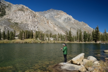 mount tom: Asian woman fishing in Horton Lake below Mount Tom in the Sierra Nevada Mountains Stock Photo