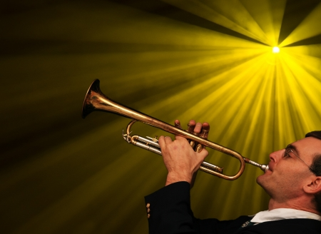 a man plays trumpet with stage lights behind him