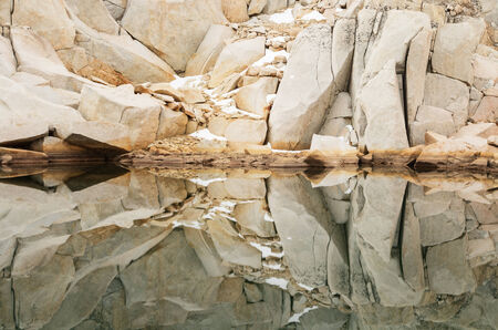 reflection of granite rocks and snow in a still mountain lake Stock Photo - 24317004