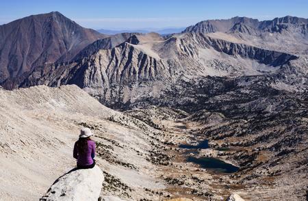 john muir wilderness: mujer sentada en la cima de una monta�a mirando a la vista de la monta�a de Sierra Nevada