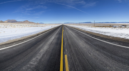 highway 6: a straight open section of highway 6 road in Nevada stretches on to the distant horizon in the winter Stock Photo