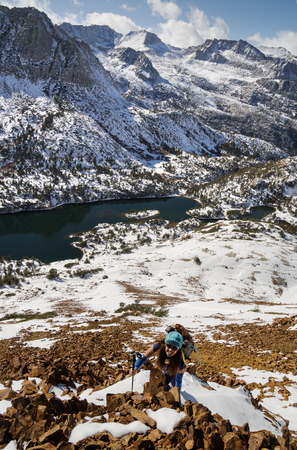 Woman climbing up Chocolate Peak in the Sierra Nevada Mountains with Long Lake below her Stock Photo - 24317144