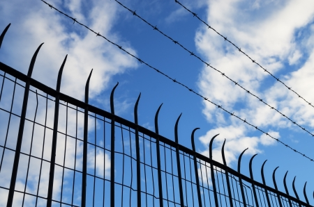 spiked: spiked and barb wire mesh fence silhouette Stock Photo