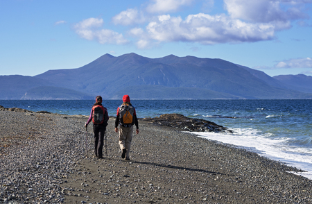 couple trekking on a beach in Patagonia along the straits of Magellan