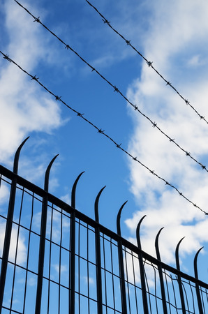 wire mesh: barbed wire and spiked mesh and bar fence silhouette with sky background