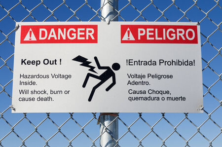 keep out: danger hazardous voltage keep out sign in English and Spanish on a fence with blue sky