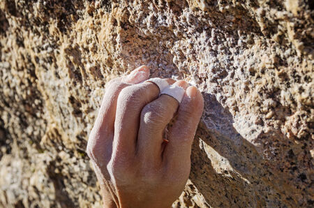 rockclimber: the hand of a woman climber in a crimp grip grabbing a small granite rock climbing hold