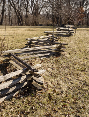 split rail: zig zag split rail fence crossing a field towards trees Stock Photo