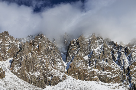 ripper: the snowy cliffs of Cloud Ripper Peak obscured in clouds Stock Photo
