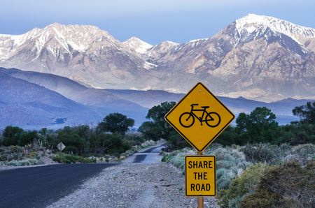 share the road with bicycles sign along a rural road leading across the Owens Valley towards distant mountains Stock Photo