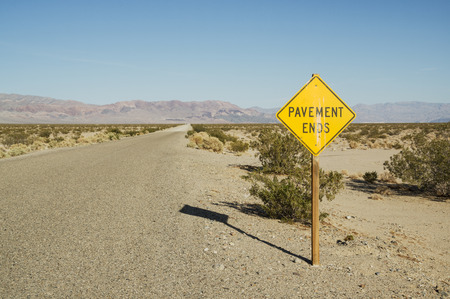 dirt road: pavement ends road sign along the Death Valley Road in California