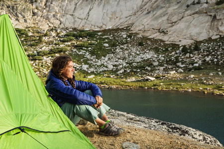 woman backpacking camper sitting next to her tent watching the sunset by Evolution Lake photo