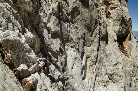 woman climbing up a steep mountain face without a rope