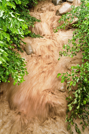 torrential: rushing muddy floodwaters in a stream bed with motion blur