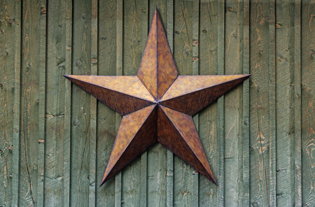 metal five pointed star on a rough wood wall