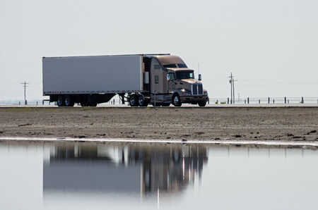 18 wheeler: tractor trailer semi  truck driving on a highway causeway with reflection in water