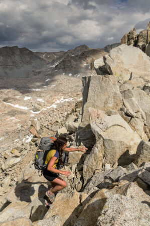 woman backpacker scrambles up snowtongue pass over Glacier Divide in the Sierra Nevada mountains