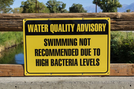 high quality: water quality advisory sign warning against swimming due to high bacteria levels