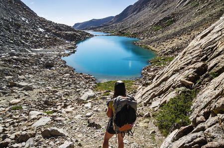 packer: back view of a woman backpacker looking down at glacial lakes in the Darwin Canyon of Kings Canyon National Park