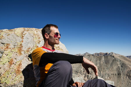 outdoorsman: middle aged man sitting on a mountain top leaning against a rock Stock Photo