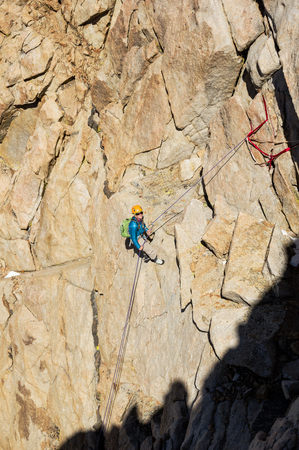rappelling: woman mountaineer rappelling down a mountain cliff Stock Photo