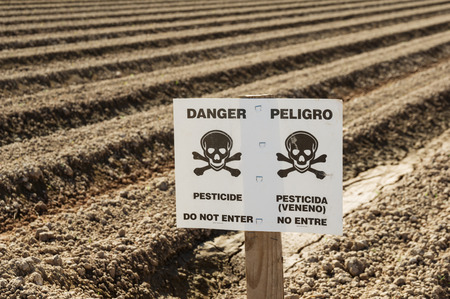 plowed field: danger pesticide sign in field ready for planting