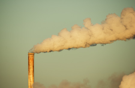 old rusty smokestack with plume of smoke lit by early morning light