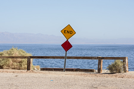 the end of the road where a road dead ends into the Salton Sea with a sign and barrier Banco de Imagens