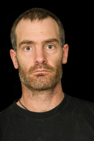 grizzled: portrait of a rugged grizzled middle aged man with black t-shirt on black background