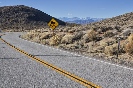 curved road with slippery road sign and distant mountains photo