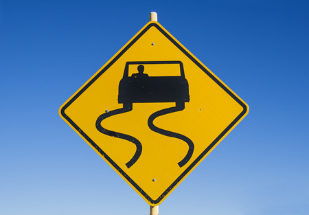 yellow and black caution slippery road sign with car and skid marks with blue sky background
