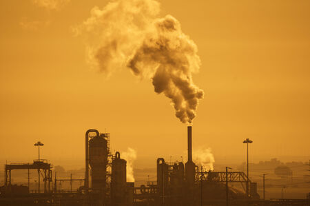 industrial plant with air pollution in a hazy orange sky Stock Photo