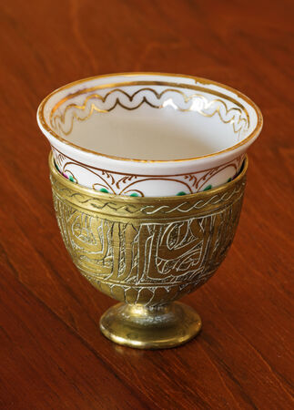 tight focus: ornate antique brass zarf with china cup on wood