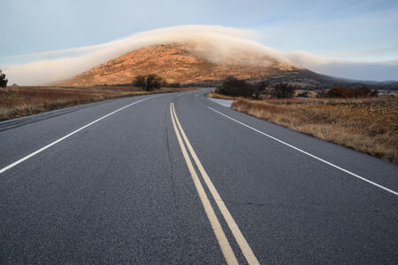 refuge: Highway 49 leads towards Mount Scott covered in fog in the Wichita Wildlife Refuge