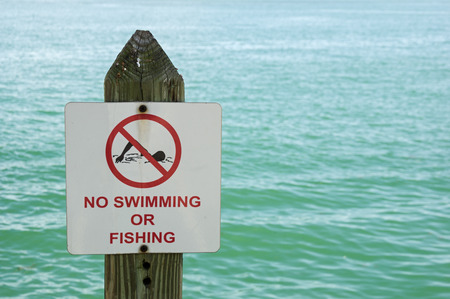 no swimming: no swimming or fishing sign on a post with out of focus water behind it Stock Photo